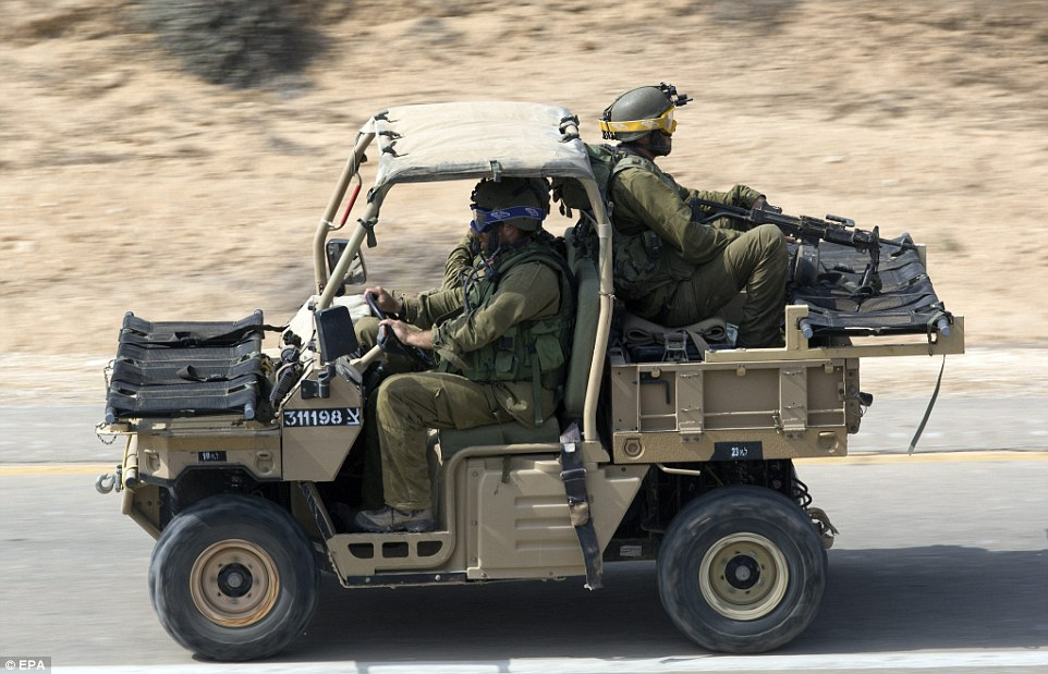 Israel soldiers on a small all terrain vehicle with two stretchers moving in southern Israel