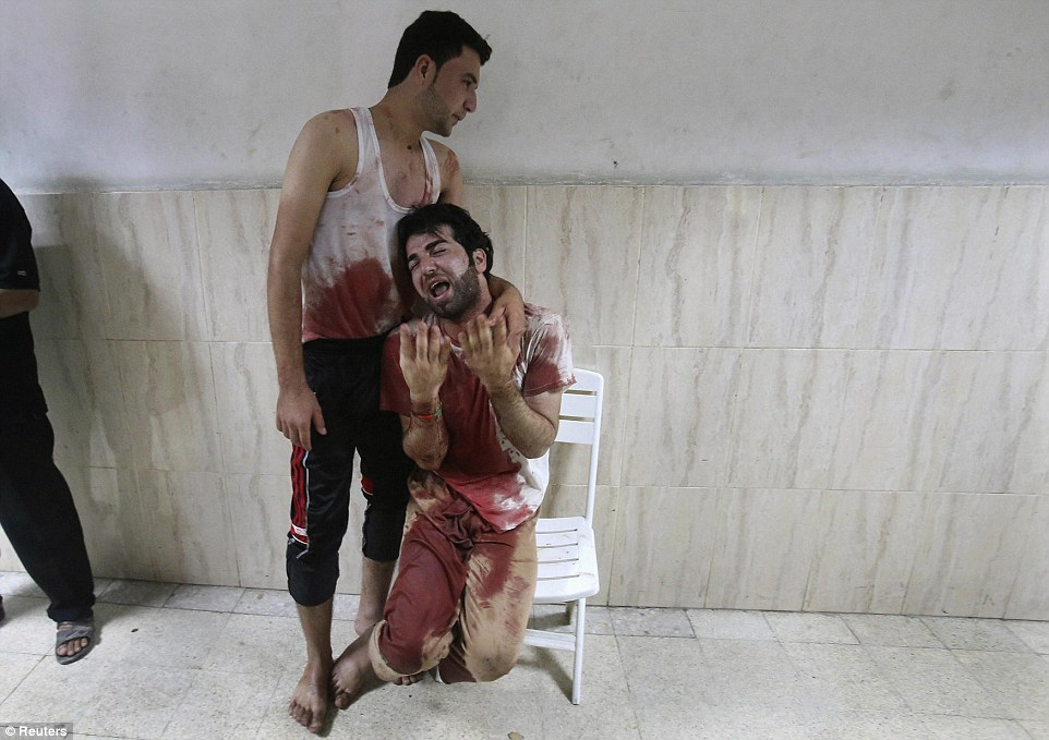 A Palestinian man, in clothes stained with the blood of his father, killed by Israeli shelling, breaks down at a hospital in Khan Younis after learning of his death