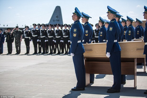 Ceremony: A coffin containing the body of an MH17 victim is loaded onto a plane for transport to the Netherlands