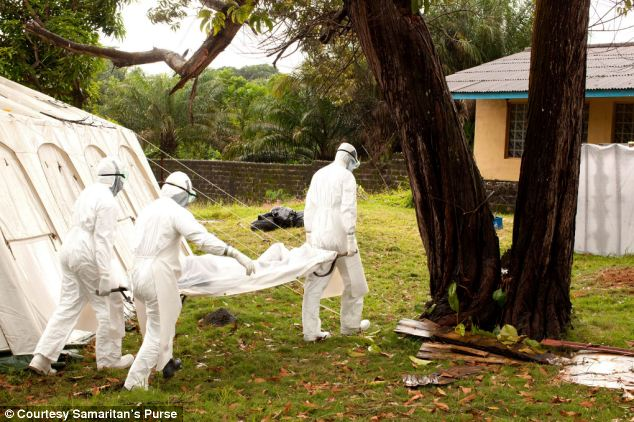 Grim: Dr Brantly helps carry the body of an Ebola victim. Once the patient dies their bodies have to be disinfected as they become highly infectious and in Liberia it is tradition to touch the dead at funerals