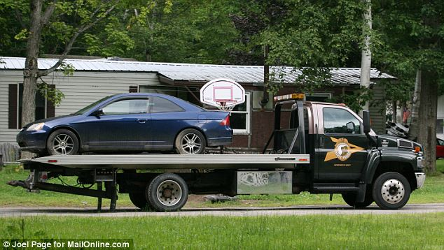 Kibby's small blue sedan was towed away on a flat bed truck as part of the collection of evidence