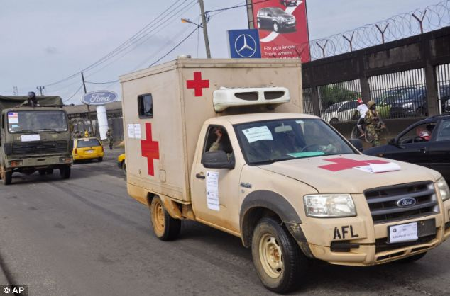 Medical vehicles in Liberia drive through the streets with posters on them saying 'Ebola must go' as the virus spreads