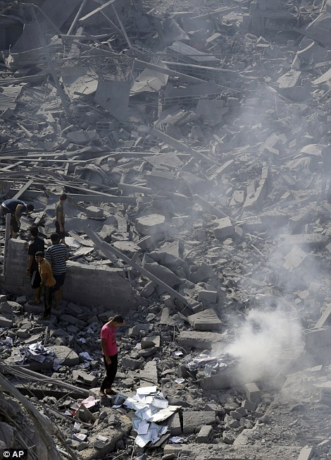 Devastation: Survivors pick over damaged copies of the Quran at theImam Al Shafaey mosque in Gaza City