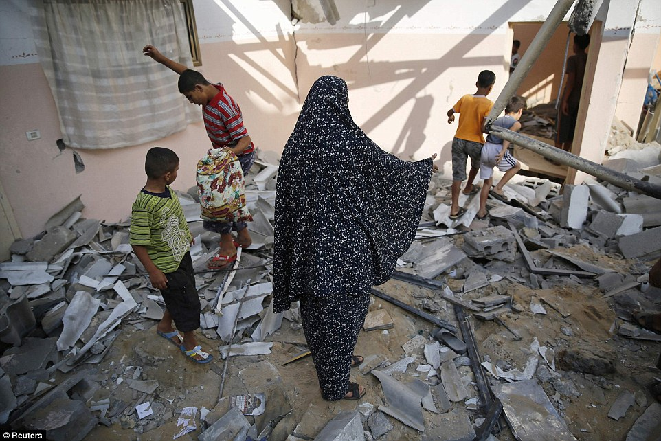 Damage: A woman and children pick over the wreckage of a home which police said was destroyd by an Israeli air strike at the Shati refugee camp in Gaza City