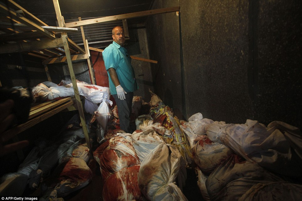 Bloodied: A medic stands among bodies which have been placed hastily in a walk-in vegetable fridge in Rafah, Gaza. Other images are too graphic to publish in full. Hamas admitted today it may have seized - but did not kill - the Israeli soldier whose alleged kidnapping yesterday morning left a 72-hour truce in tatters