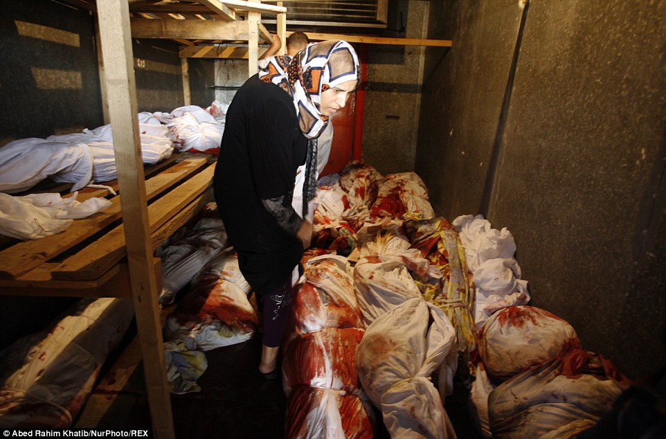 Horror: A Palestinian relative stands in the fridge today among the mass of bodies, which have been bound up in blood-stained white sheets after Israeli strikes