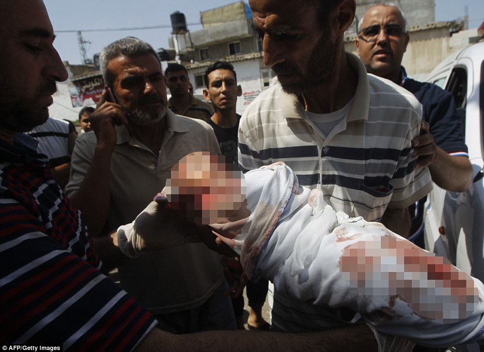 Mourning: Palestinian relatives carry the body of two month old Noor al-Saidy, killed during attacks on the Gaza Strip, during her funeral  in Rafah in southern Gaza