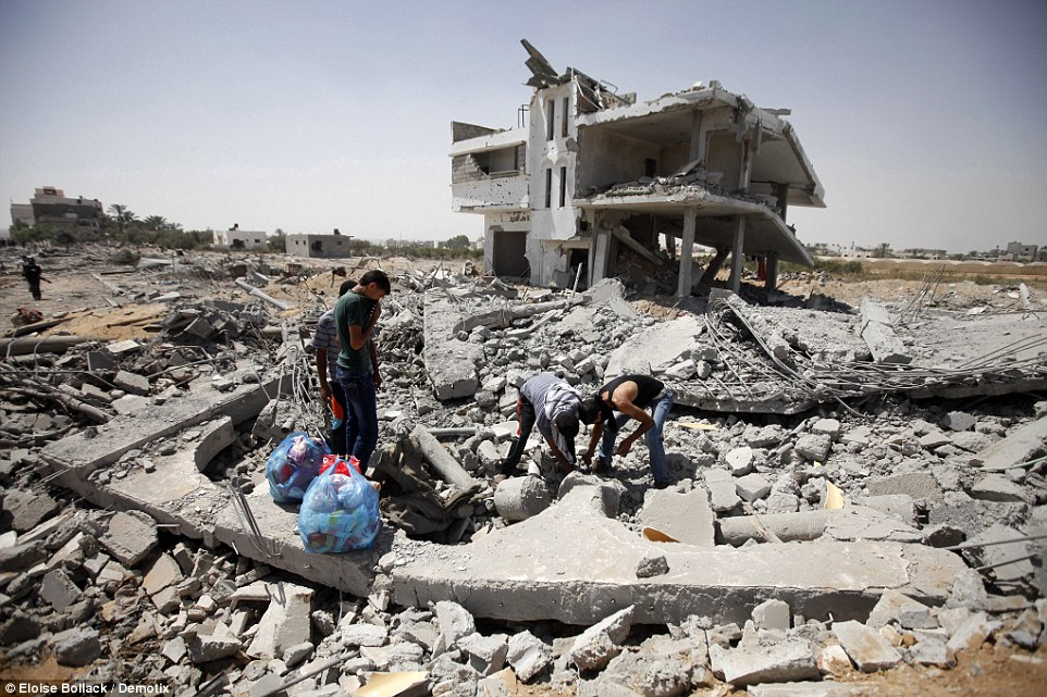 Demolished: Palestinians look for bodies under the rubble of a house demolished during the Israeli bombardment of Khuzaa in south eastern Gaza Strip