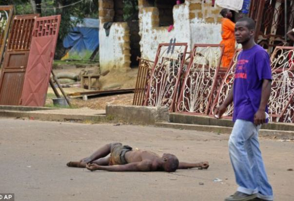 Shocking: Relatives of Ebola victims in Liberia have started dragging their loved ones' bodies out of their homes and dumping them on the streets in a bid to avoid being quarantined. Above, a man walks past the dead body
