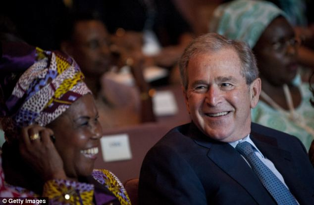 Former U.S. President George W. Bush pictured joking with one of the spouses of the African leaders at a symposium organised by Michelle Obama