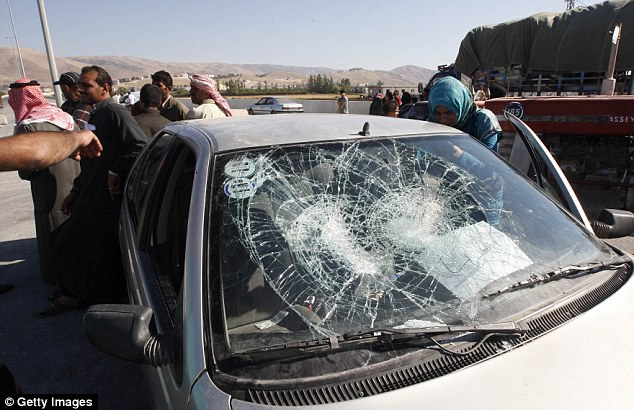 On the way out: This car, lined up with other traffic on the road out of Arsal, was damaged in the fighting