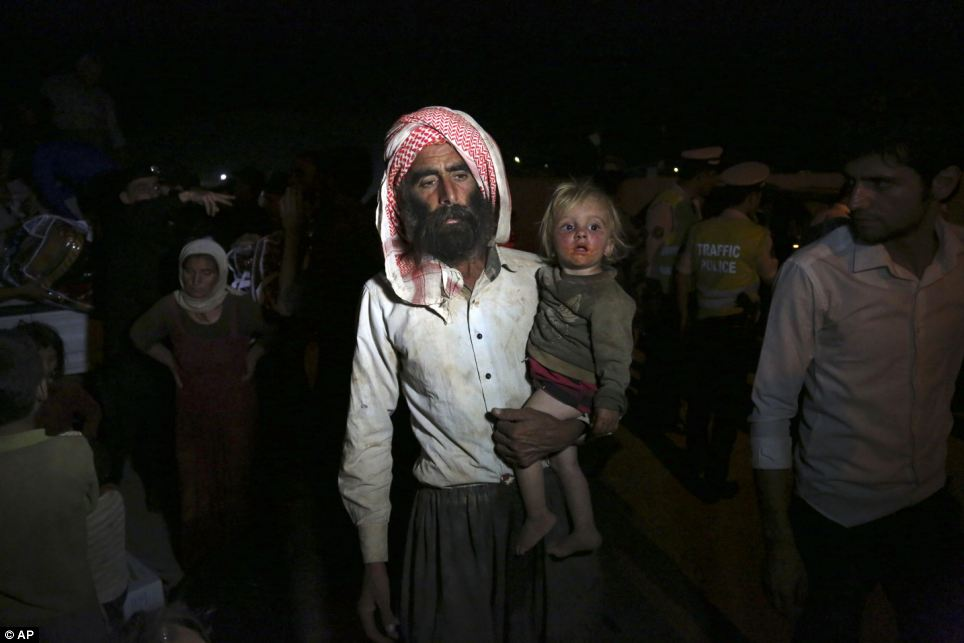 Carried: A man carries a small child as Yazidis cross the border into Syria at the Feeshkhabour border point in northern Iraq after leaving the Sinjar mountains