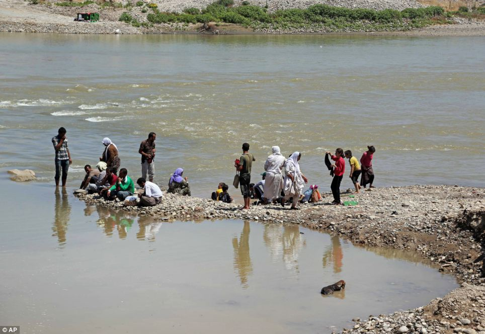 Displaced Iraqis from the Yazidi community cool themselves in the Tigris River at Feeshkhabour border point, northern Iraq