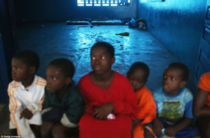 Children sit in the isolation ward as the disease continues to spread in West Africa