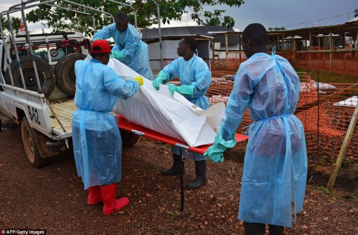 An Ebola victim is loaded on to a truck by a government burial team at a facility in Kailahun in Sierra Leone