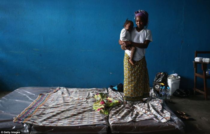 A mother and child stand on top of a mattress in an Ebola isolation station in Liberia for suspected victims of the virus