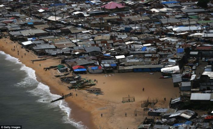 Fishermen pull a dugout from the water in the impoverished neighbourhood of West Point in Monrovia, Liberia. People in the area suspected of contracting the Ebola virus are being brought by health workers to a temporary isolation centre