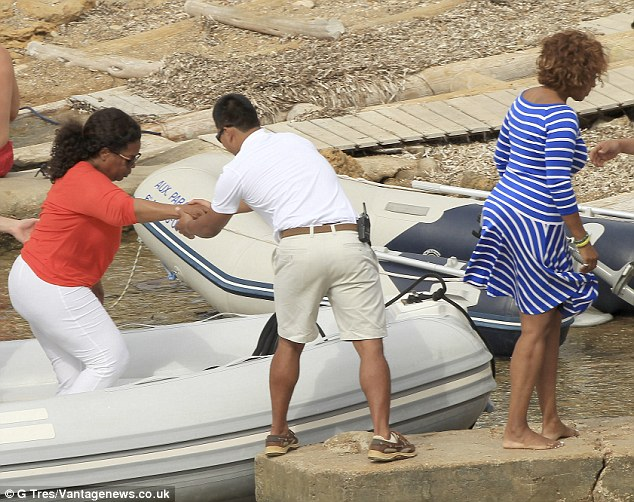 Pure shores: Oprah is helped out of a speedboat as they prepare for a day of sightseeing