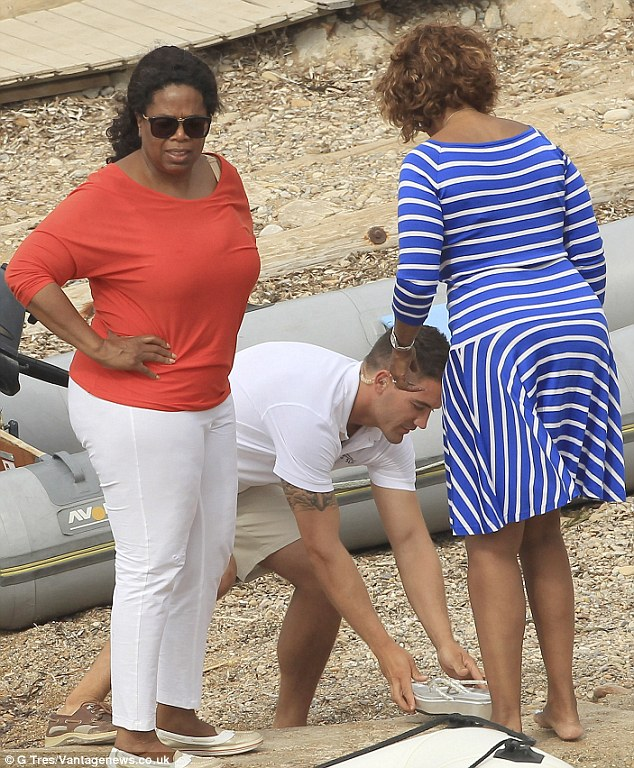Royal treatment: Gayle gets her shoe placed on her foot by a minder