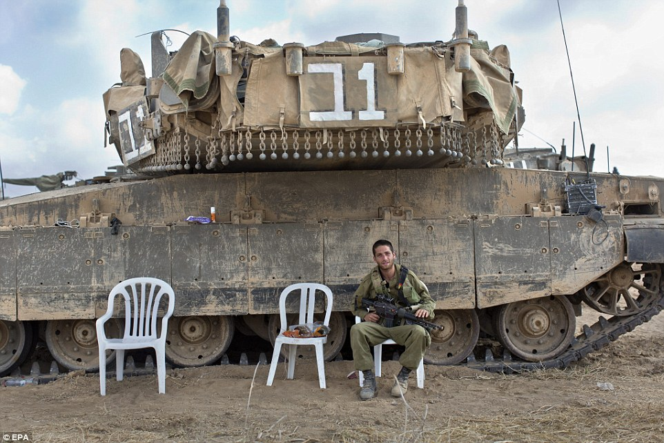Combat: An Israeli soldier sits next to a Merkava tank in a staging area in southern Israel, along the border with the Gaza Strip. The Israeli military said three rockets had been fired from the Gaza Strip into southern Israel despite a ceasefire