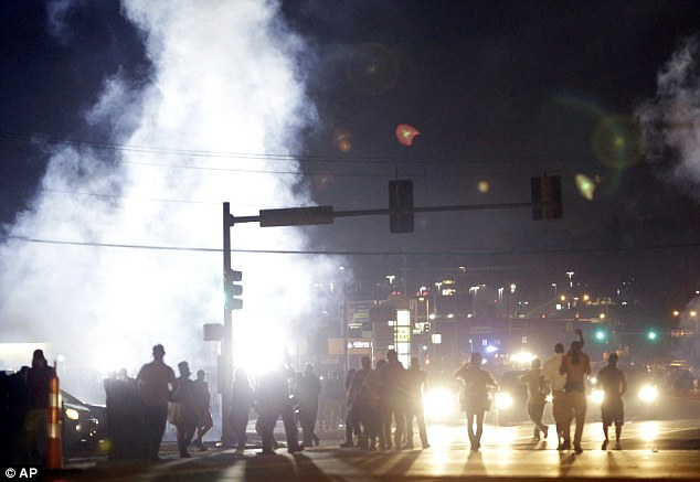 Violence: The jihadists and their sympathisers in the West have taken to Twitter to send messages of support to hundreds of demonstrators taking part in a ninth night of angry protests in Ferguson (pictured)