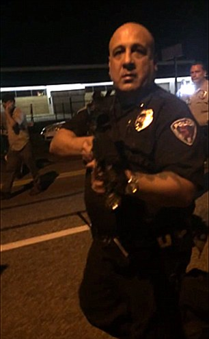 An unnamed police officer from St. Ann, Missouri, has been relieved of duty and suspended indefinitely after he was caught on camera pointing an assault rifle at a protester, in Ferguson, on Tuesday night