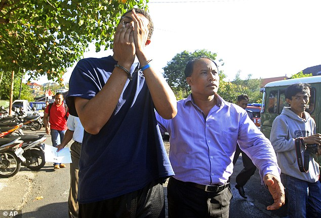 An Indonesian police officer escorts American Tommy Schaefer (left) as he is brought to the police station for questioning in relation to the death of his girlfriend's mother