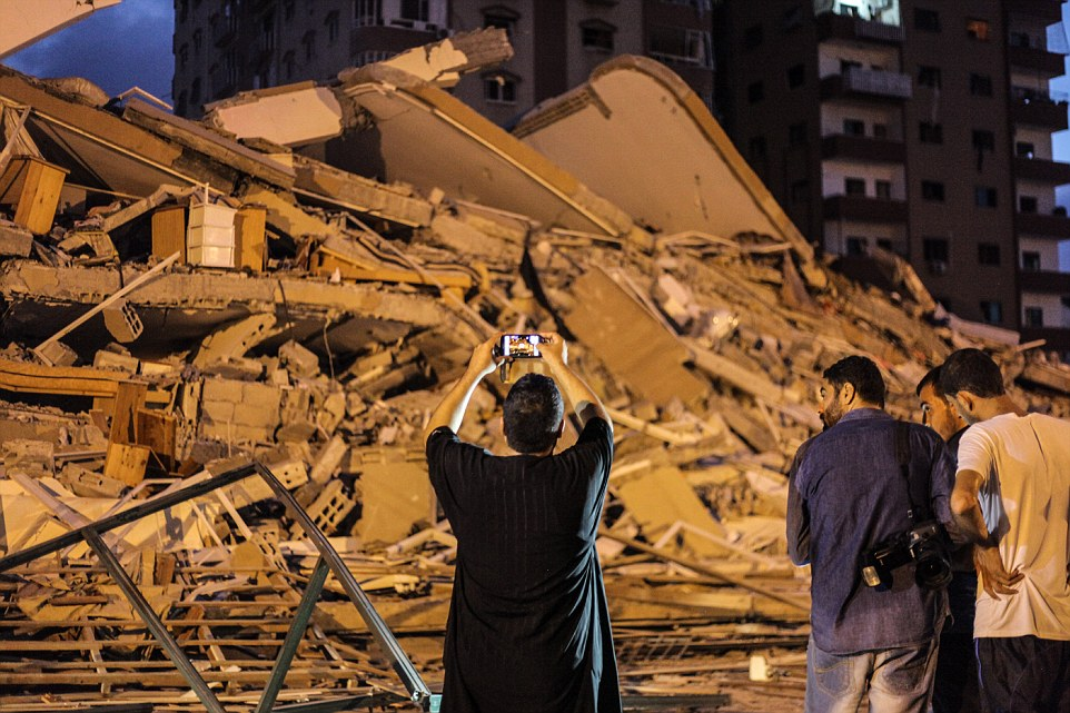 Surveying the damage: Palestinians inspect the site as one man takes pictures of the devastating damage on his mobile phone