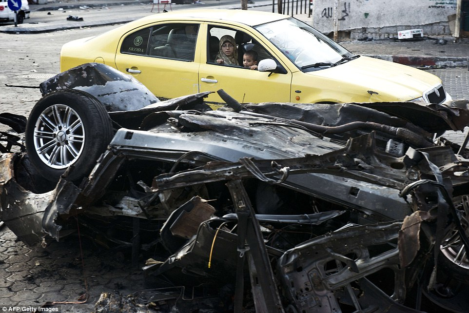 Gutted: A Palestinian woman and child look at the charred remains of a car that was targeted by an Israeli airstrike in Gaza City this morning