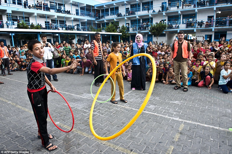A welcome distraction: The children try to forget their problems by playing with hoops in the grounds of the school