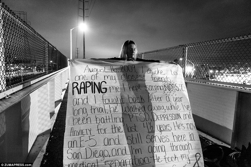 Heartbreaking: Melissa Bania holds a banner on the foot bridge across from the entrance to Naval Station San Diego. The sexual assault victim is part of a photo essay by Mary Calvert called The Battle Within: Sexual Violence In America's Military
