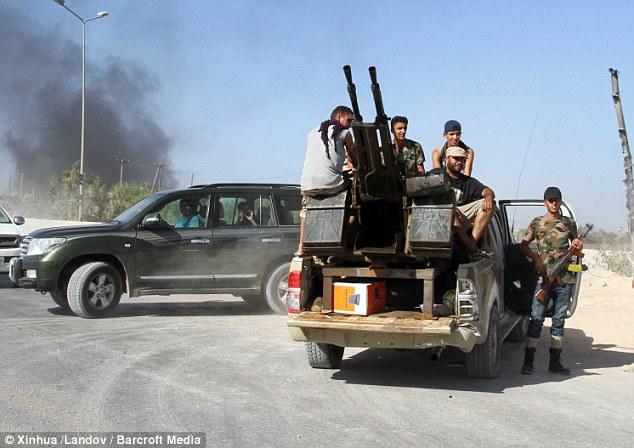 Militants aube assis dans un camion monté avec des canons anti-aériens à la porte de l'aéroport international de Tripoli le dimanche