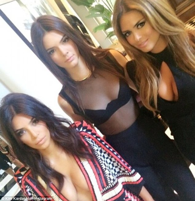 Party time: Kendall and Kim posed with a pal as they perfected their smouldering looks before the awards