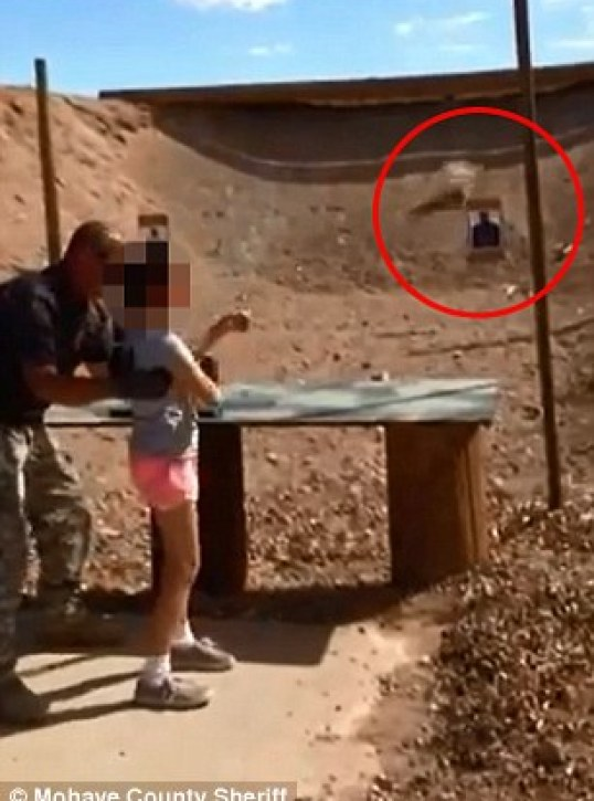 Tragic: This screen grab shows the split second before the nine-year-old girl shoots Charles Vacca in the head. In the frame, the girl can clearly be seen to have lost her double handed grip on the Uzi as it recoils after firing. Her left hand is prized free as bullets fire (seen hitting behind the target circled in red). The gun is in her right hand and is clearly moving towards Vacca