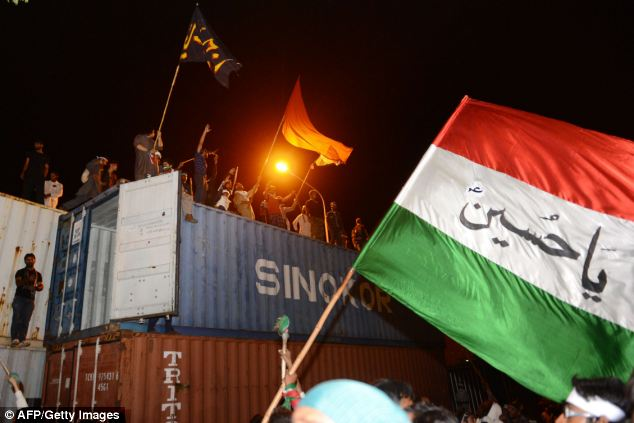 Supporters of cricketer-turned-politician Imran Khan and Canadian cleric Tahir ul Qadri, climb a container which was used to block the way of the prime minister's house in Islamabad