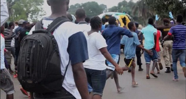 Anger: Furious Monrovia residents chase the vehicle down the road as a warning to the man not to return