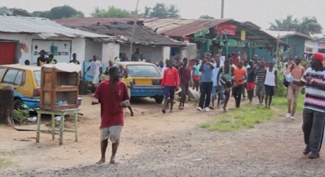 Fear: The hungry Ebola patient (red shirt) wandered into the market to get food, causing shoppers to panic