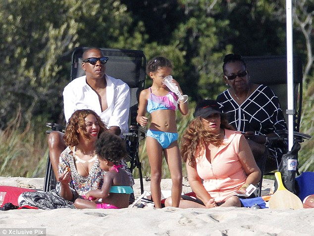 Family time: Beyonce covered up her enviable figure in a black and white muumuu that bared her cleavage as she sat on a blanket in the sand next to her adorable daughter