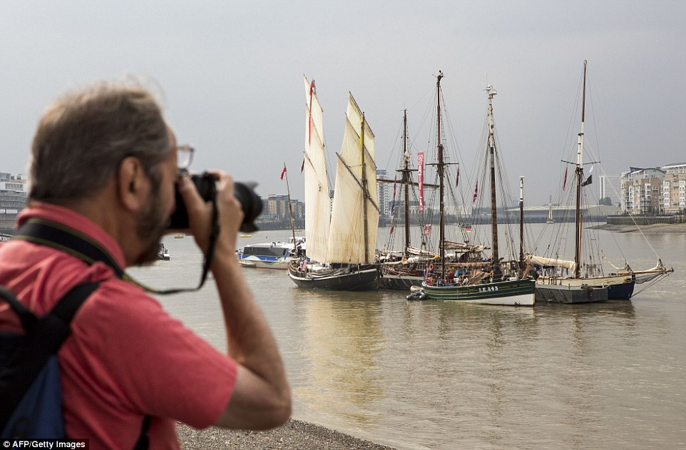 A man takes pictures of the ships. The imposing ships have from around the globe, including from Spain, Holland, Portugal, Poland and Russia
