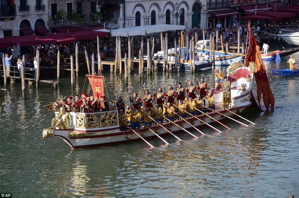 A bordo do Bucintoro, um pequeno grupo de trompetistas anunciam o início da procissão.  Uma grande bandeira do Veneto está atrás na água enquanto multidões se reúnem em pranchas de madeira deterioradas e barracas flutuantes