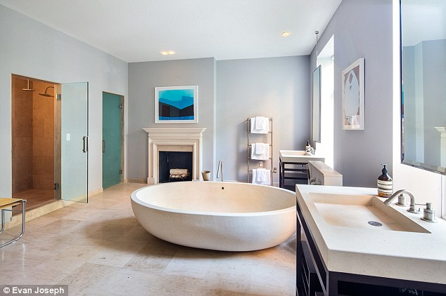 The size of a studio: The bathroom has two completely separate sinks, and amazing natural looking yet ultra-modern round stone bath in the room's centre, a shower with multiple shower heads and its own fireplace