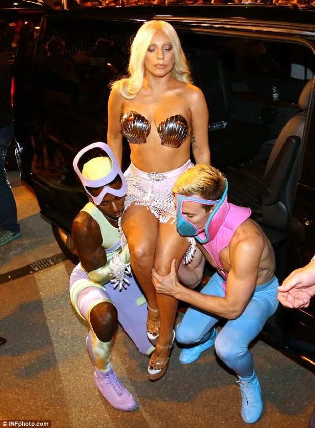 She's loving it: Gaga sat on two men's shoulders as they got ready to hoist her up