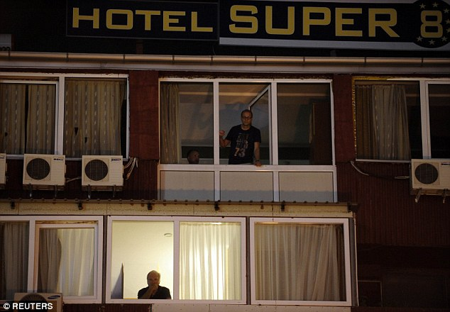 People look from the window of the quarantined hotel in Skopje where the unnamed British man was staying