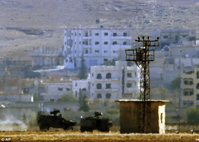 Calamity: An Islamic State flag (top centre, in black) flies above Kobane on the border of Turkey and Syria