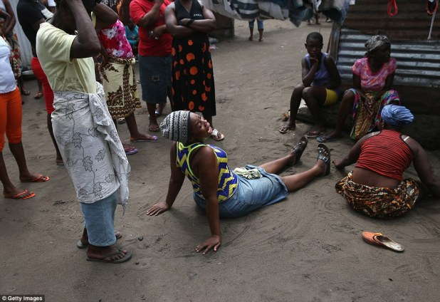 Devastating effects: A woman grieves as Ebola burial team members arrive to take away the body of Mekie Nagbe, 28, for cremation