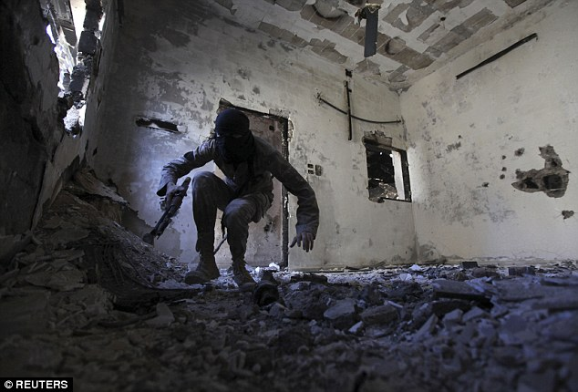 Stealth tactics: A guerrilla fighter moves inside a damaged house in the Syrian province of Deir al-Zor. Groups of Syrians are now hunting down ISIS militants in response to the terror group's growing brutality (file image)