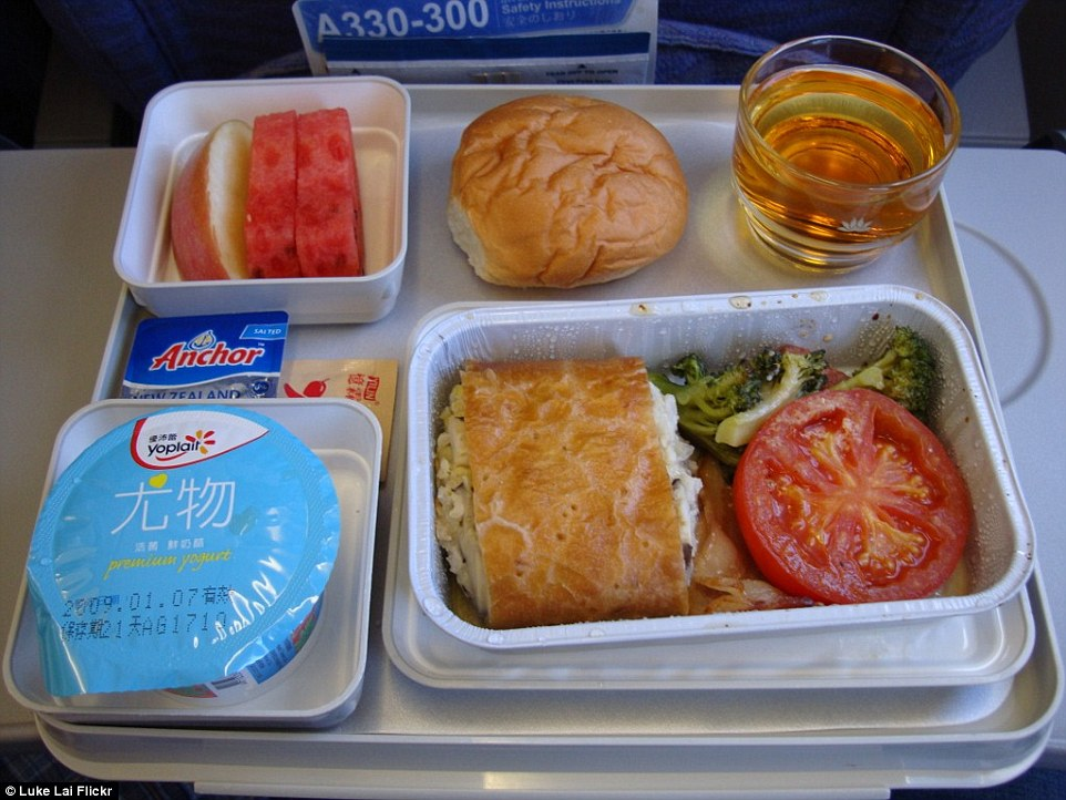 A meal served on a Vietnam Airlines flight from Taoyuan, Taiwan to Ho Chi Minh City, Vietnam. A serving of yoghurt, three slices of fruit and what appears to be salmon en croute served with tomato and broccoli, and a bread roll is on offer for economy passengers