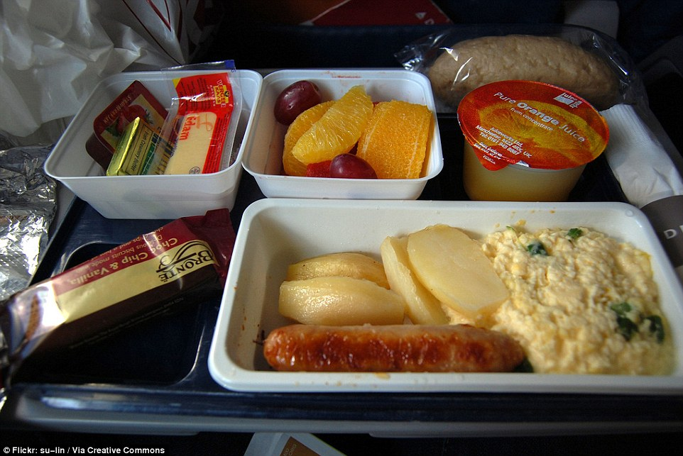 Economy breakfast on a Delta Airlines flight from London to New York of scrambled eggs, wedges, sausage, fruit salad and orange juice