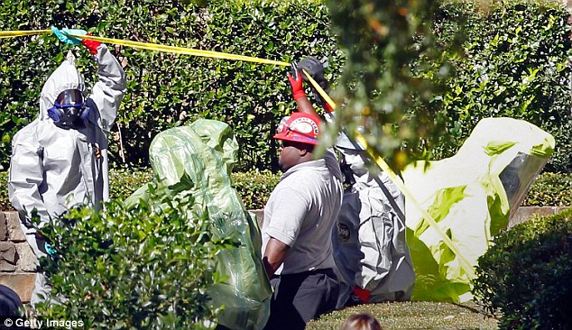 Workers put on full hazmat gear to clean up the apartment of Amber Vinson, the second sick nurse, on Thursday