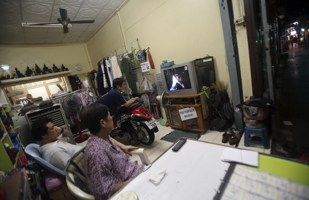 In this Sept. 30, 2014 photo, a Thai family watches a soap opera on television in Bangkok, Thailand. A recent real-life rape and murder of a 13-year-old girl on an overnight train in Thailand has focused national outrage on Thai popular culture, and particularly TV soaps for sending messages that trivialize - and some say encourage - rape. (AP Photo/Sakchai Lalit)